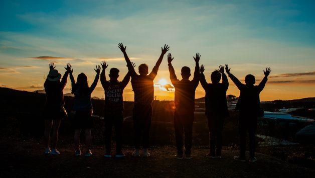 Vriendengroep of collega's bij zonsondergang tijdens een bedrijfsfeest