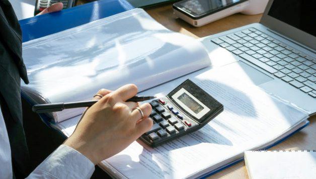 man met calculator en laptop